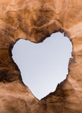 Heart shaped burnt out of a paper Stock Images