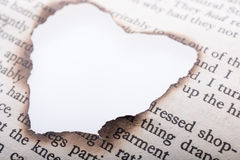 Heart shaped burnt out of texted  paper Stock Photography