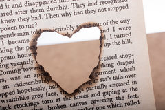 Heart shaped burnt out of texted  paper Stock Photos