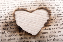 Heart shaped burnt out of texted  paper Royalty Free Stock Image