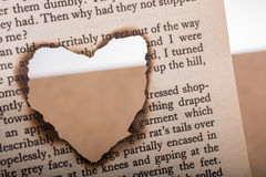 Heart shaped burnt out of texted  paper Stock Image