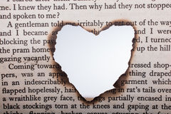 Heart shaped burnt out of texted  paper Royalty Free Stock Images