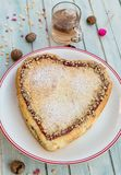 Heart shaped cake. Freshly baked heart shaped cake with jam and nuts and a cup of tea Stock Photography
