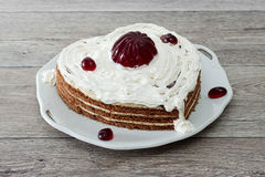 Heart shaped cake with red marmalade served on vintage dish against wooden background Stock Photo