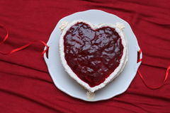 Heart shaped cake with red marmalade served on vintage dish on red drapery Royalty Free Stock Photo