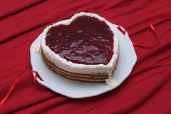 Heart shaped cake with red marmalade served on vintage dish on red drapery Stock Photos