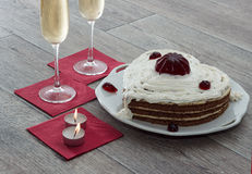 Heart shaped cake with red marmalade, two glasses of champagne and two candles served on napkins against wooden background for rom Stock Photo