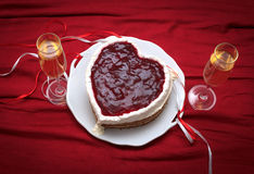 Heart shaped cake with red marmalade on vintage dish and two glasses of champagne served on red drapery Stock Photo