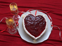 Heart shaped cake with red marmalade on vintage dish and two glasses of champagne served on red drapery Stock Photos