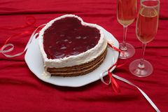 Heart shaped cake with red marmalade on vintage dish and two glasses of champagne served on red drapery Royalty Free Stock Image