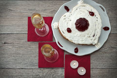 Heart shaped cake with red marmelade, two glasses of champagne and two candles served on napkins against wooden background for rom Royalty Free Stock Photo