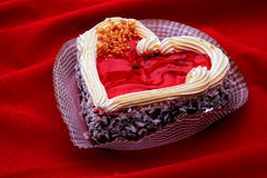 Heart-shaped cake on the red velvet Royalty Free Stock Photo