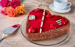 Heart shaped cake with roses. On wooden table Stock Photo