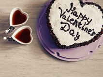 Heart-shaped cake for St. Valentine`s Day. And two cups in the shape of a heart stock images