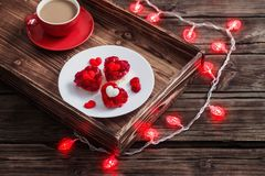 Heart-shaped cakes and cup of coffee on wooden table. Heart-shaped red cakes and cup of coffee on old wooden table stock image