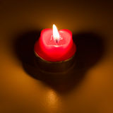 Heart-shaped candle. Heart-shaped burning candle casting a hart-shaped shadow Stock Images