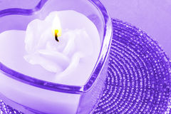 Heart shaped candle. A closeup of a glass candle holder with a white wax rose candle Stock Photos