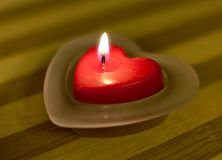 Heart-shaped candle with flame Royalty Free Stock Photo