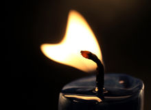 Heart shaped candle flame. On black Stock Photography
