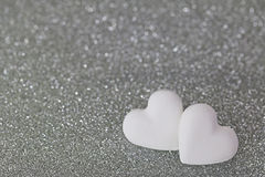 2 heart shaped candy pills on silver glittery background Stock Photos