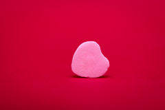 Heart Shaped Candy on Red. A pink heart shaped candy lies on its side on a red textured background Royalty Free Stock Photos