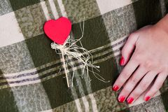Heart shaped candy and woman's hand. Woman's hand and red heart-shaped candy on the checked plaid Royalty Free Stock Photo