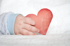 Heart shaped card in baby hand Stock Photos
