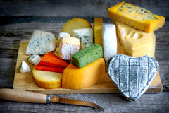 Heart shaped cheese on old boards colorful food abstract Stock Photo