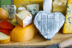 Heart shaped cheese on old boards colorful food abstract Royalty Free Stock Photo
