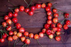 Heart shaped cherries. Juicy rainer cherry on wooden table heart shaped Stock Images