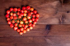 Heart shaped cherries. Juicy rainer cherry on wooden table heart shaped Stock Photos