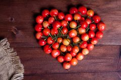 Heart shaped cherries on wooden table. Juicy rainer cherry on wooden table heart shaped Royalty Free Stock Images
