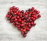 Heart shaped from cherry on white wooden background. Royalty Free Stock Photography