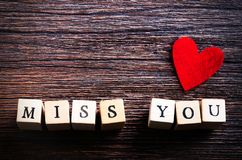Heart shaped chewing candies and words miss you on cubes, wooden background. Free space for your text. Heart shaped chewing candies and words miss you on cubes Stock Photography