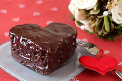 Heart shaped chocolate cake and a bouquet. Heart shaped chocolate cake with heart decoration and bouquet Royalty Free Stock Photography