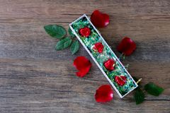Heart shaped chocolate candy in box and rose. On wood background royalty free stock images