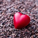 Heart shaped chocolate candy on crushed cocoa nibs. Close up. Copy space. royalty free stock image