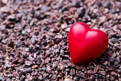 Heart shaped chocolate candy on crushed cocoa nibs. Close up. Copy space. stock photo