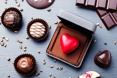 Heart shaped chocolate candy in a gift box on slate background. Top view. royalty free stock images