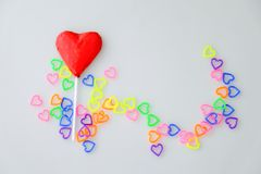 Heart shaped chocolate candy with red wrappings. And colorful mini heart toy plastic on white background stock image