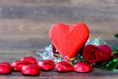 Heart shaped chocolate candy with red wrappings. And red rose on wood background stock images