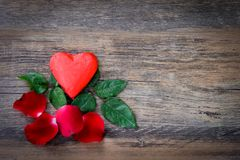 Heart shaped chocolate candy with red wrappings. And red rose on wood background stock photos