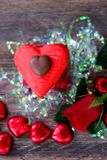 Heart shaped chocolate candy with red wrappings. And red rose on wood background royalty free stock photography