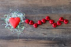 Heart shaped chocolate candy with red wrappings. On wood background stock photos