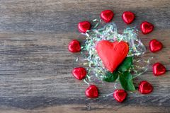 Heart shaped chocolate candy with red wrappings. On wood background royalty free stock image