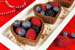 Heart shaped chocolate cups filled with fresh berries Stock Images