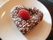 Heart-shaped chocolate tart dessert. A heart-shaped chocolate tart cake with a raspberry and powdered sugar and on a white plate. This French dessert pastry is Royalty Free Stock Photos