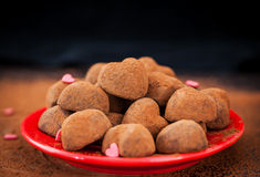Heart shaped chocolate truffles on red plate Stock Images