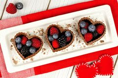 Heart shaped chocolates filled with berries with red cloth Royalty Free Stock Images