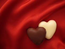 Heart-shaped chocolates on red. Silk background Royalty Free Stock Image